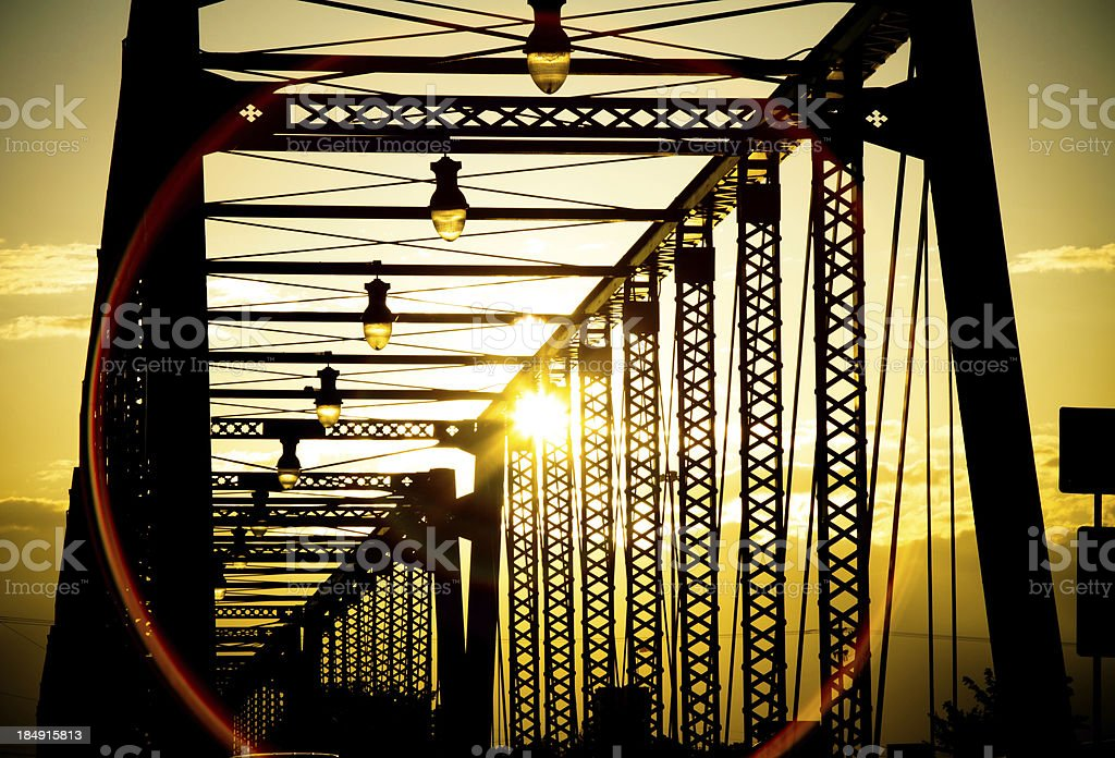 Old silhouetted bridge at sunset stock photo