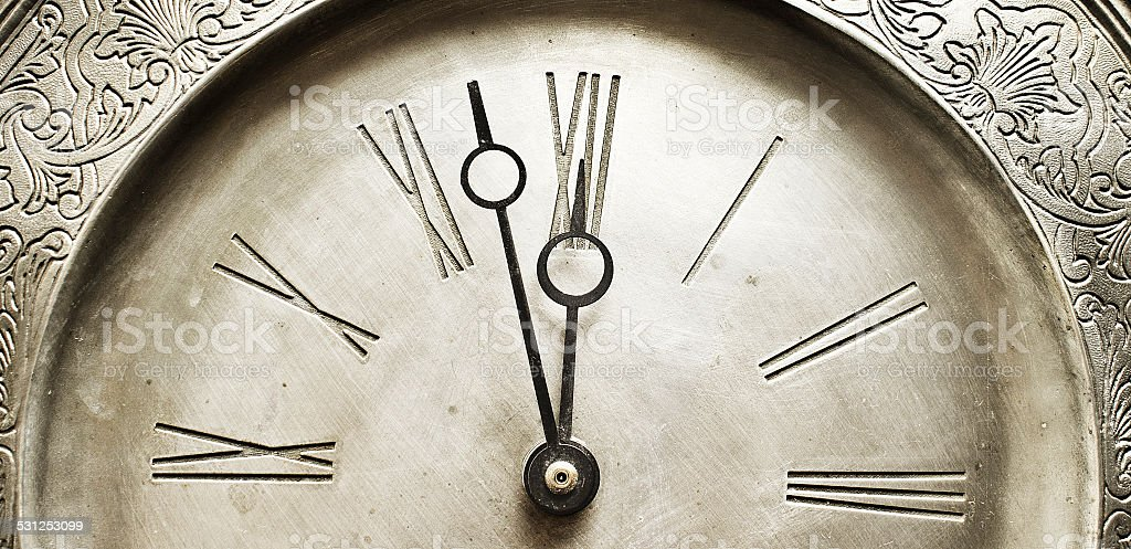Old silver clock with roman numbers indicating it's about time. stock photo
