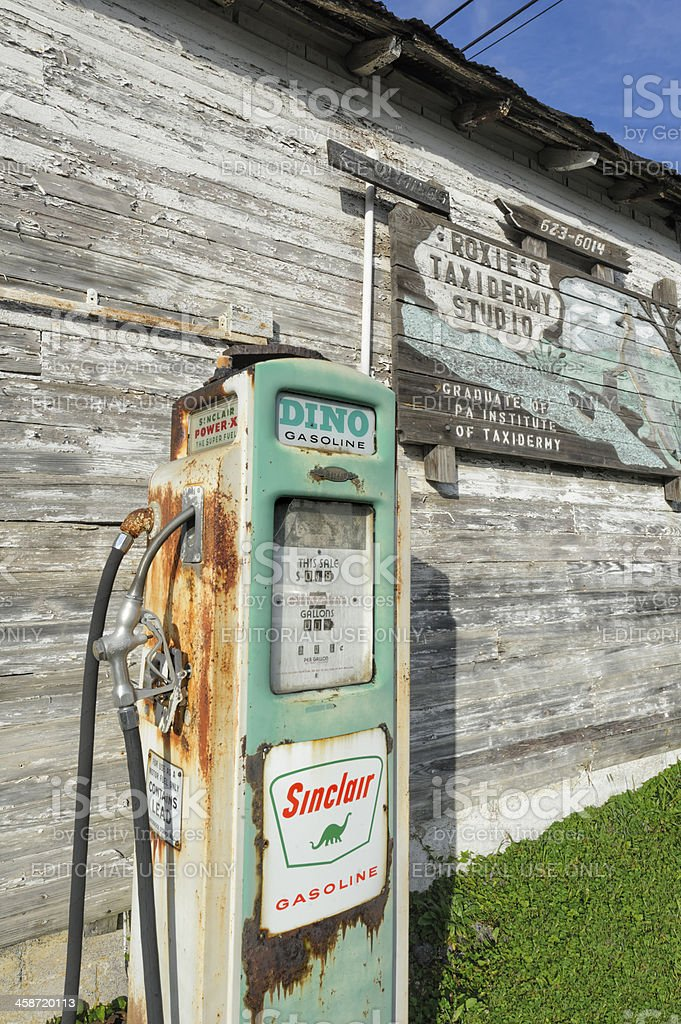 Old Sinclair Dino Gas Pump and Weathered Farm Building stock photo
