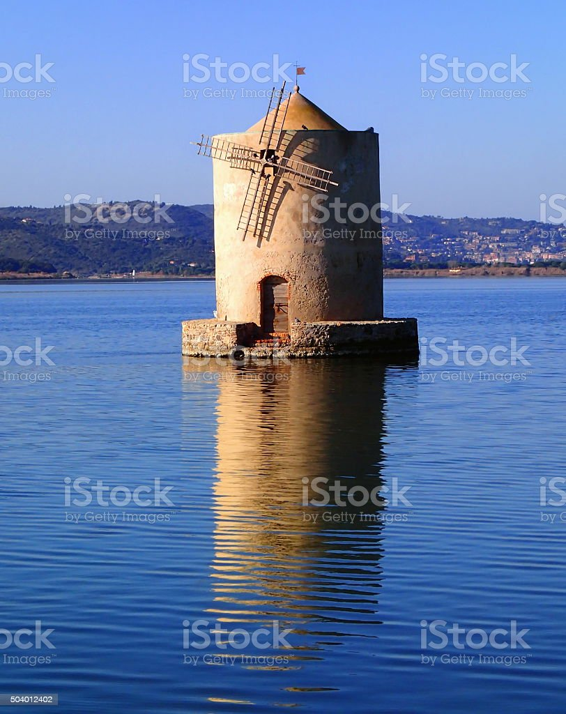 Old slanted windmill in water stock photo