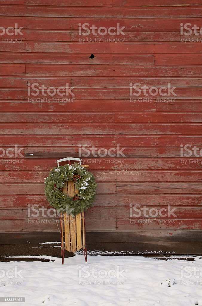 Old Sled Against Red Barn stock photo