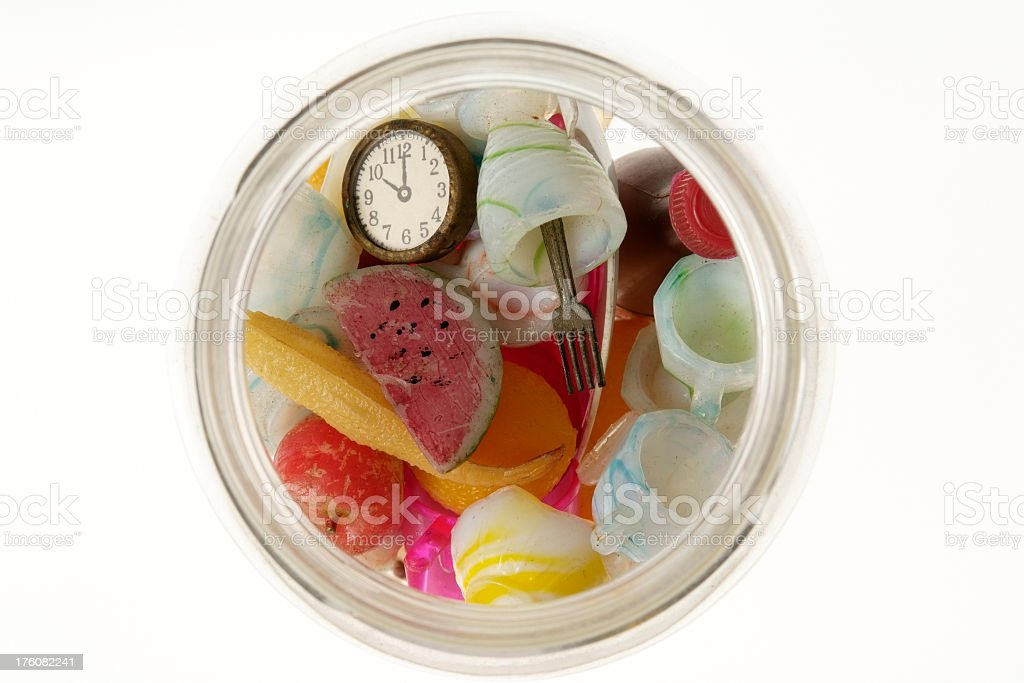 Old small toy in a glass jar on white background royalty-free stock photo