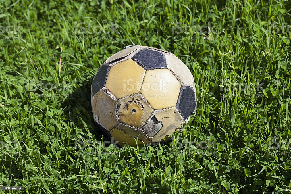 Old soccer ball on green grass stock photo