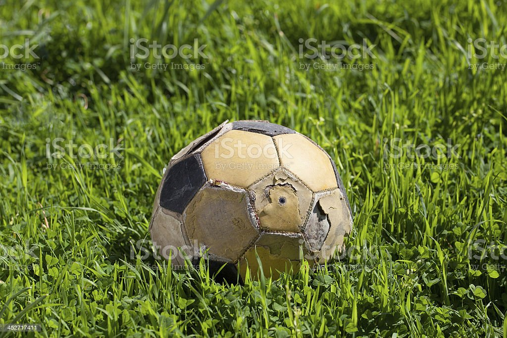 Old soccer ball on green grass royalty-free stock photo