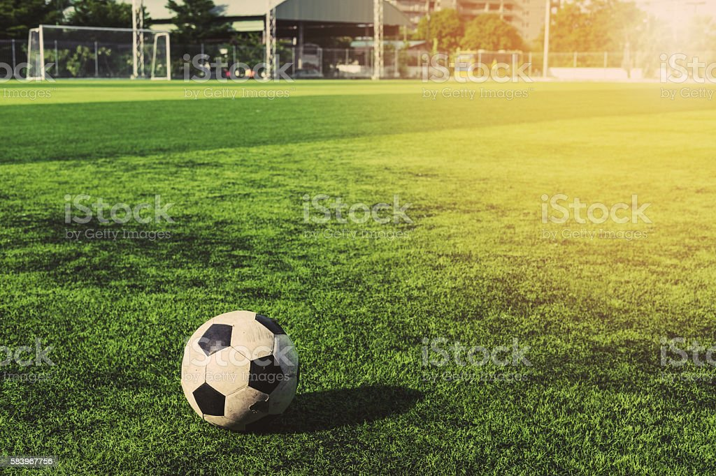 Old soccer ball on green grass, vintage tone stock photo