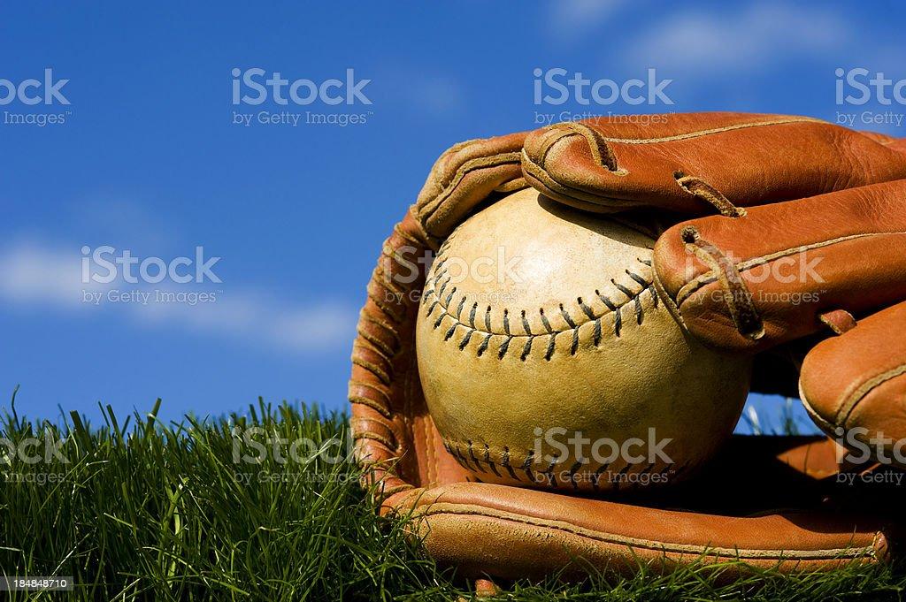Old Softball in worn glove sitting on grass stock photo