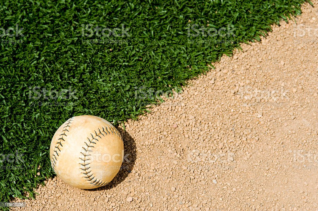 An Old Softball sitting between the infield grass and dirt of a...