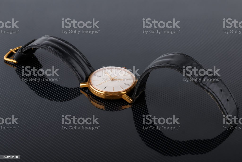 old soviet wristwatch on black glossy background stock photo