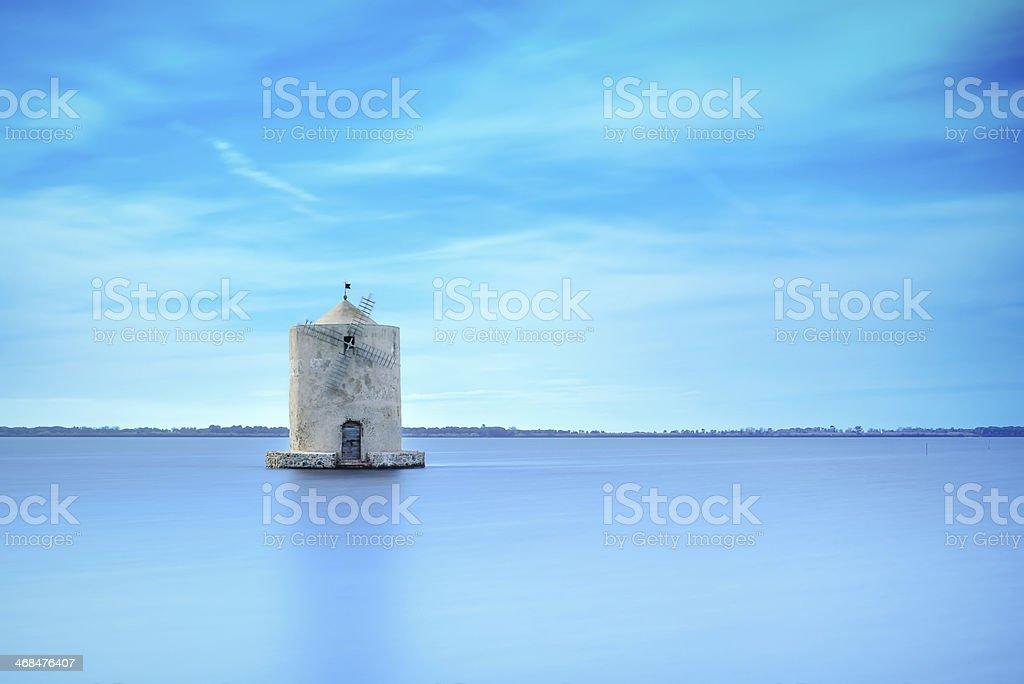 Old spanish windmill in a blue lagoon. Orbetello, Argentario, Italy. stock photo