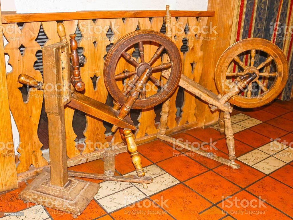 Old spinning wheel on wooden stock photo