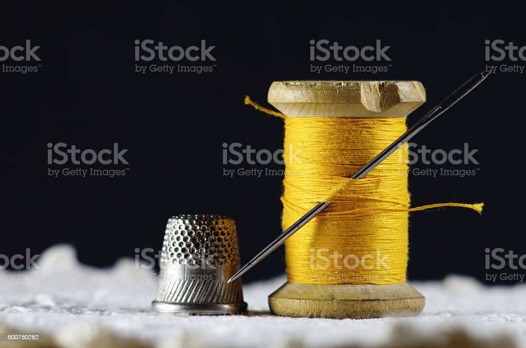 Old spool of thread with needle closeup stock photo
