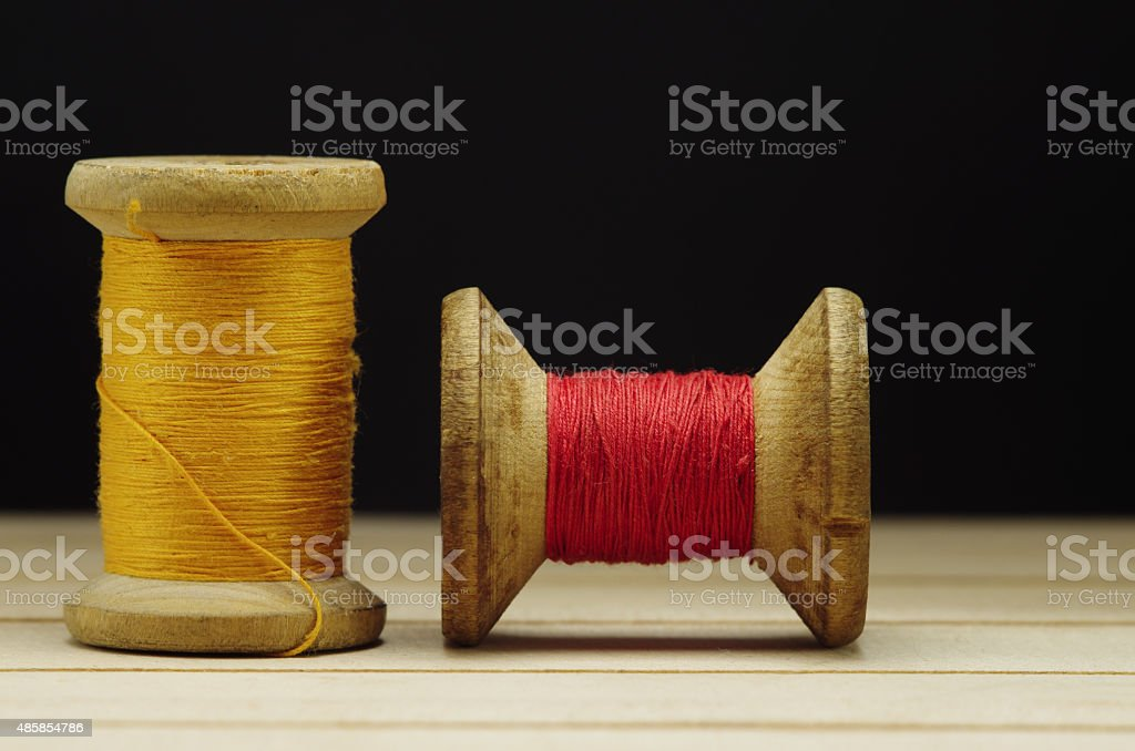 Old spool of thread with needle closeup. Tailor's work stock photo