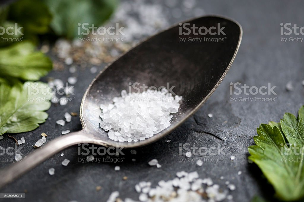 Old spoon rock salt parsley stock photo