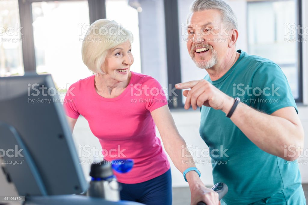 old sport couple training on treadmill in fitness class for senior people stock photo