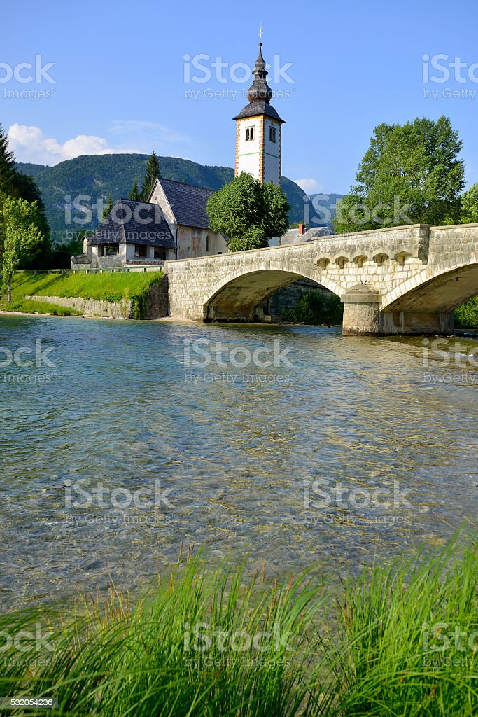 Old St. John church and stone bridge at Bohinj lake stock photo