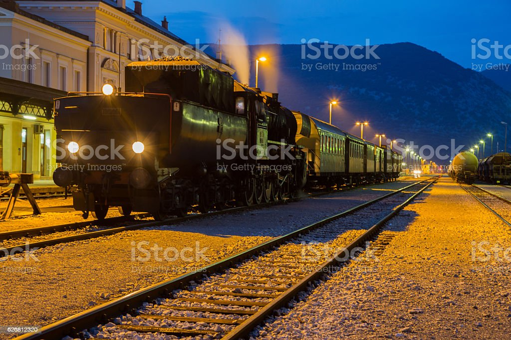 Old steam train at night on the station stock photo