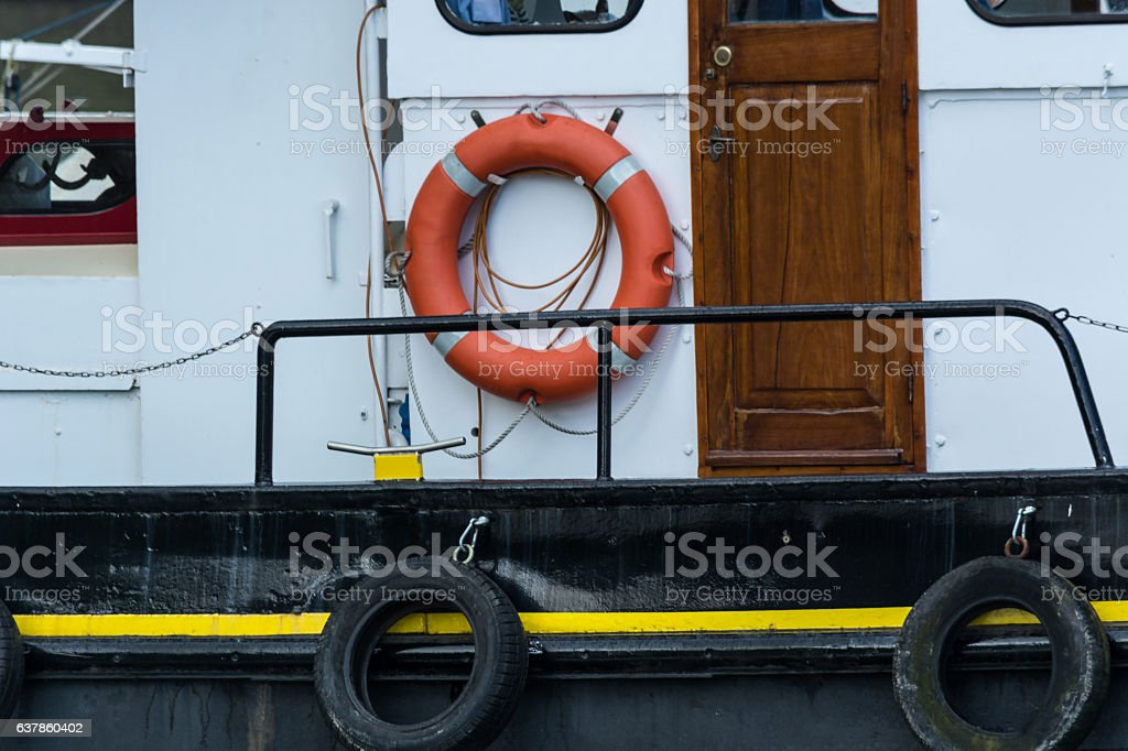 Old steel boat with lifebuoy stock photo