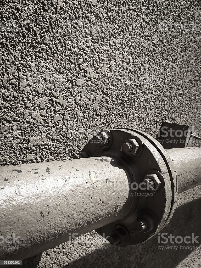 Old steel pipes on rough wall. stock photo