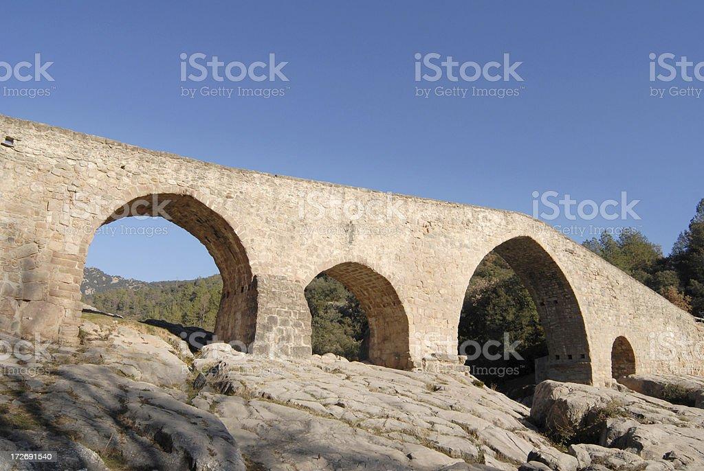 old stone bridge crossing river Llobregat stock photo