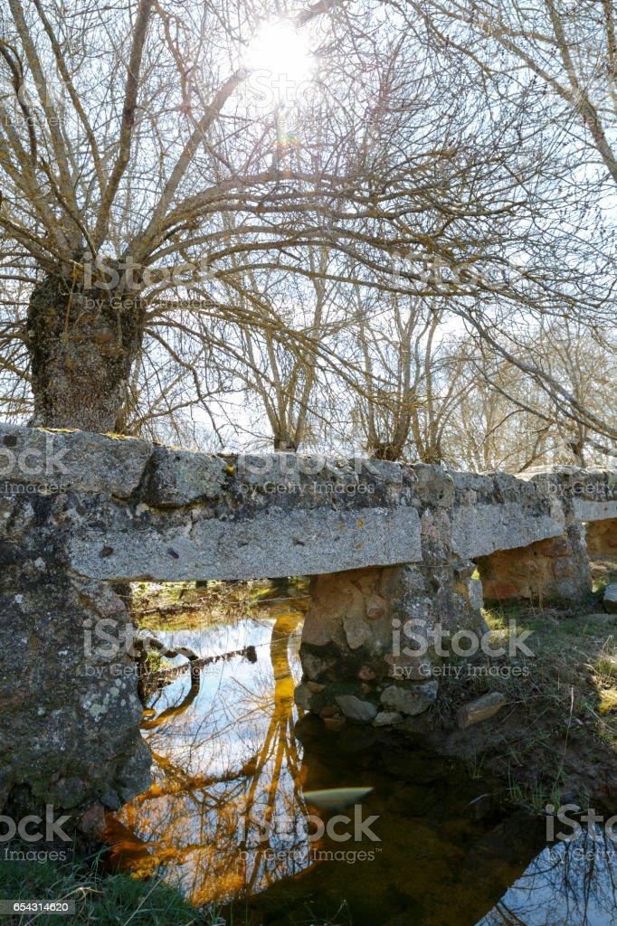 Old stone bridge over a river stock photo
