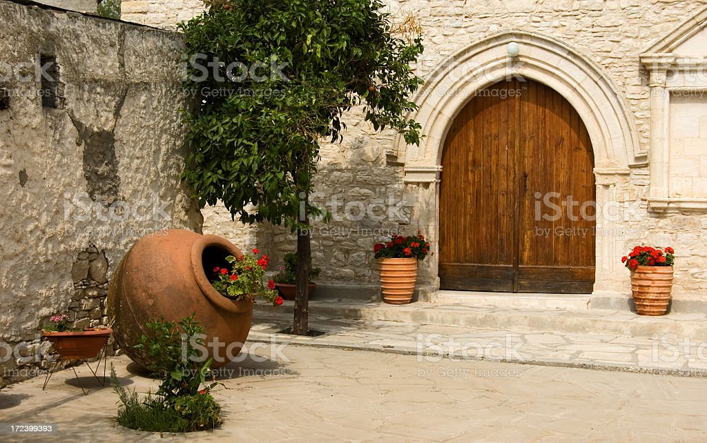 Old stone courtyard with potted plants and wooden doorway royalty-free stock photo