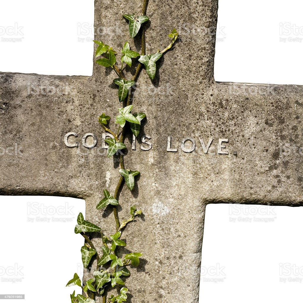 Old stone cross inscribed 'God is Love' on white background royalty-free stock photo
