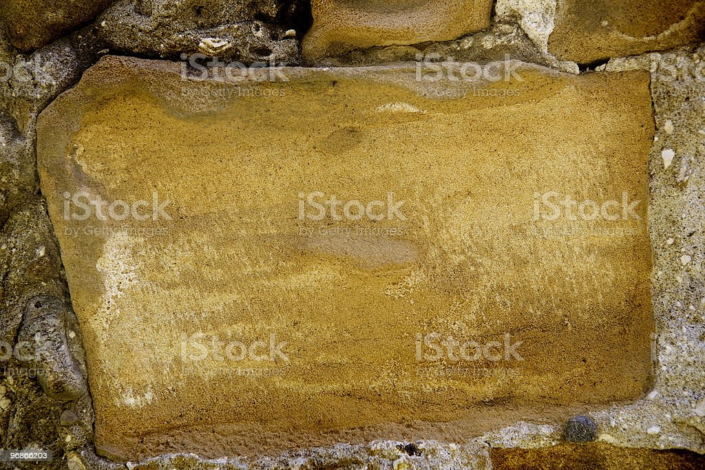 Old stone in a fence made of sandstone. stock photo