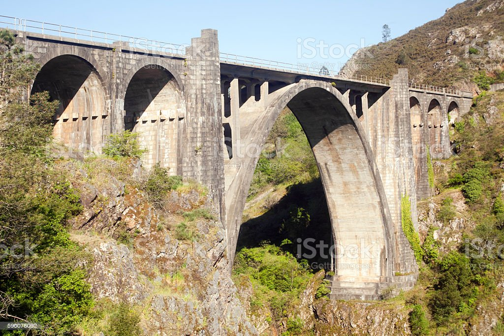 Old stone railway bridge, mountain forest and blue sky. stock photo