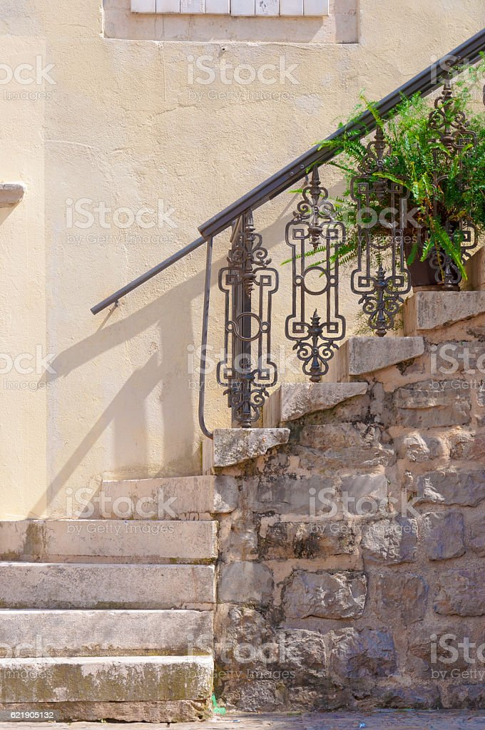 Old stone stair with wrought iron railings. stock photo