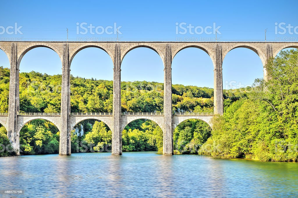 Old stone viaduct over large river between two hills HDR stock photo