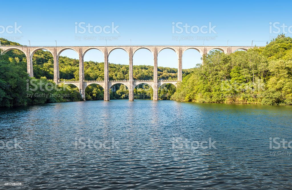 Old stone viaduct over large river between two hills panorama stock photo