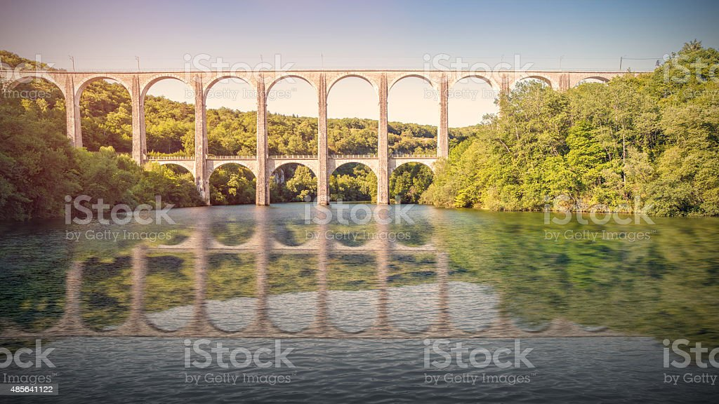 Old stone viaduct over large river between two hills sunset stock photo