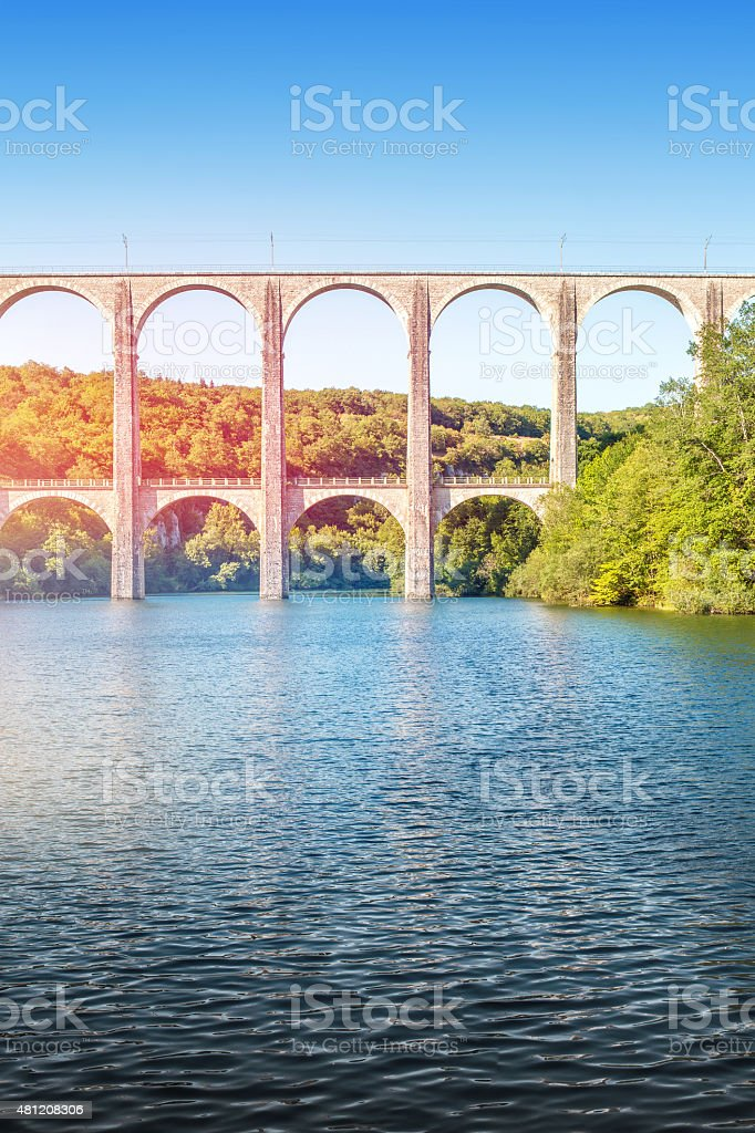 Old stone viaduct over large river between two hills vertical stock photo