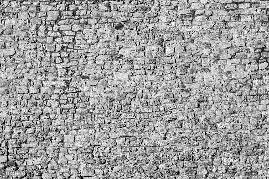 Old stone wall background, black and white stock photo