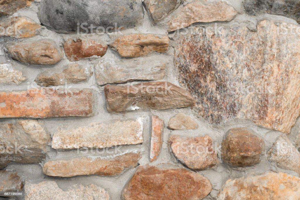 Old stone wall of multicolored granite stock photo