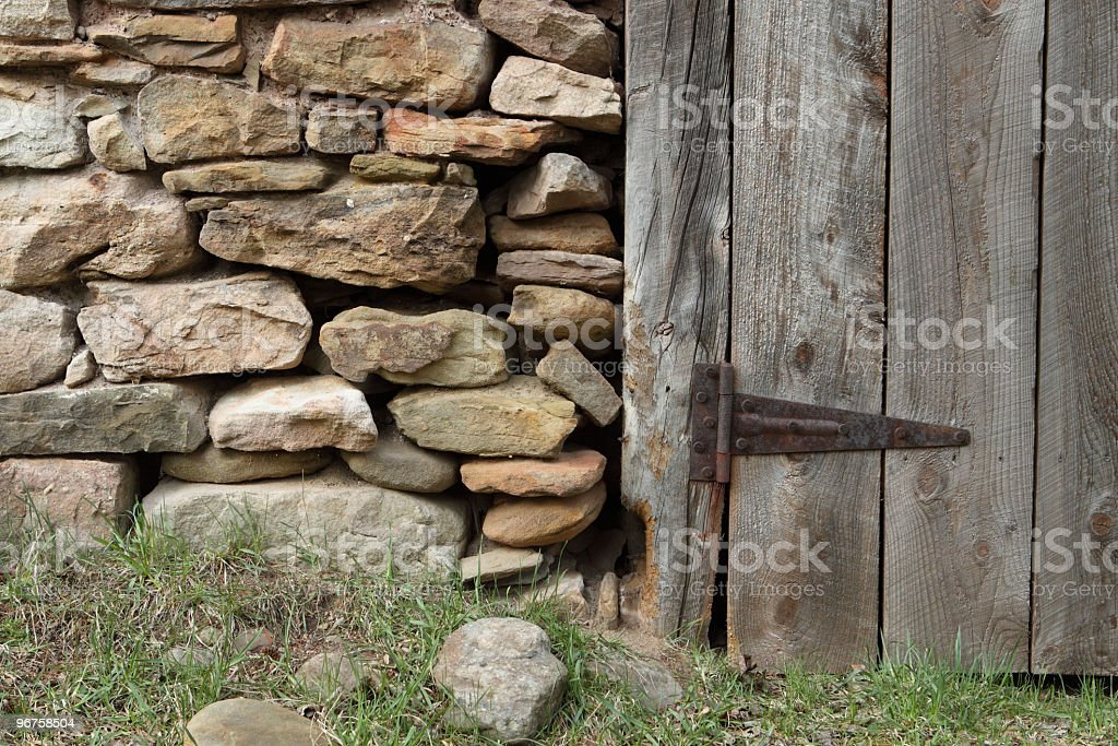 Old Stone Wall With Rustic Wood Door royalty-free stock photo