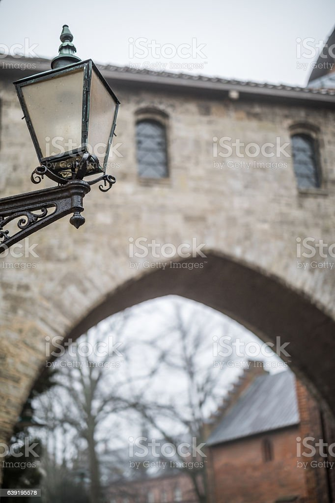 Old street lamp in front of Bishop Absalons arch stock photo