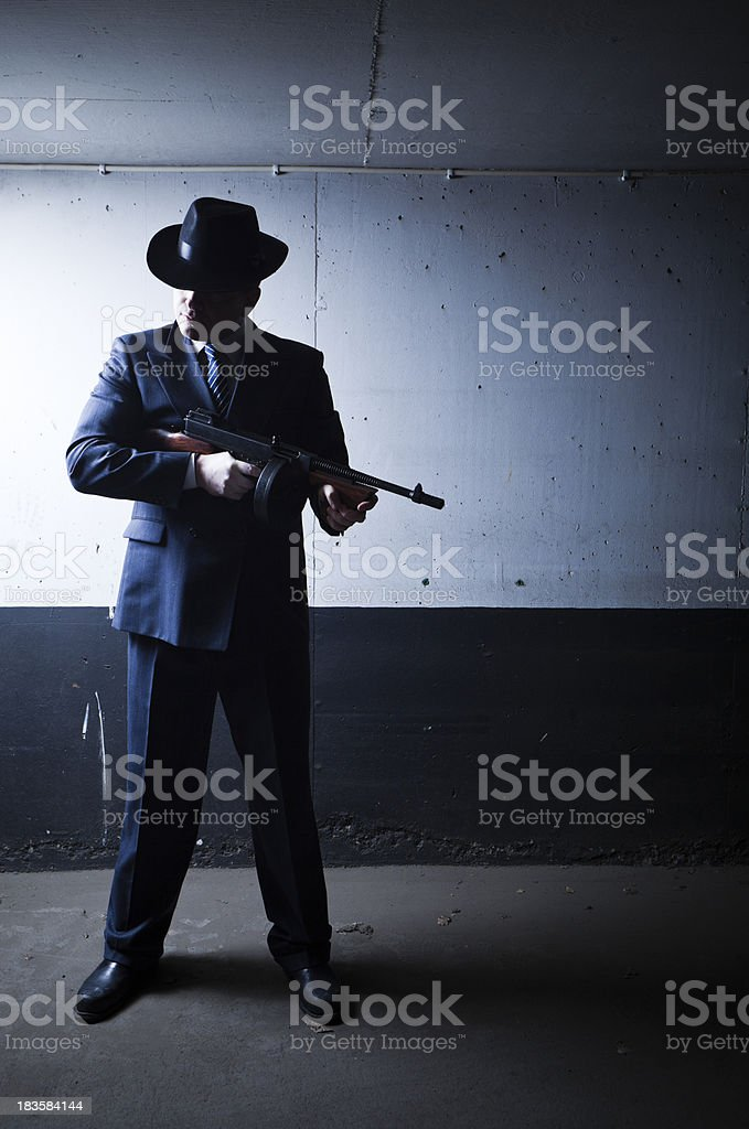 Old style gangster with tommy gun in dark setting stock photo