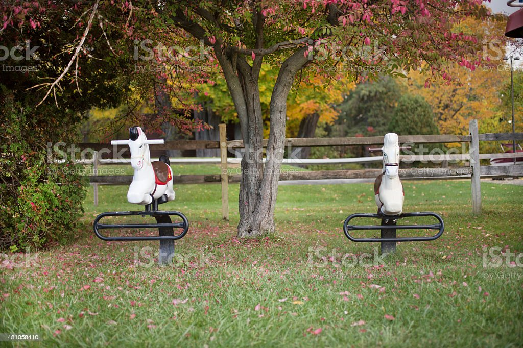 Old style horse ride on playground at the park stock photo