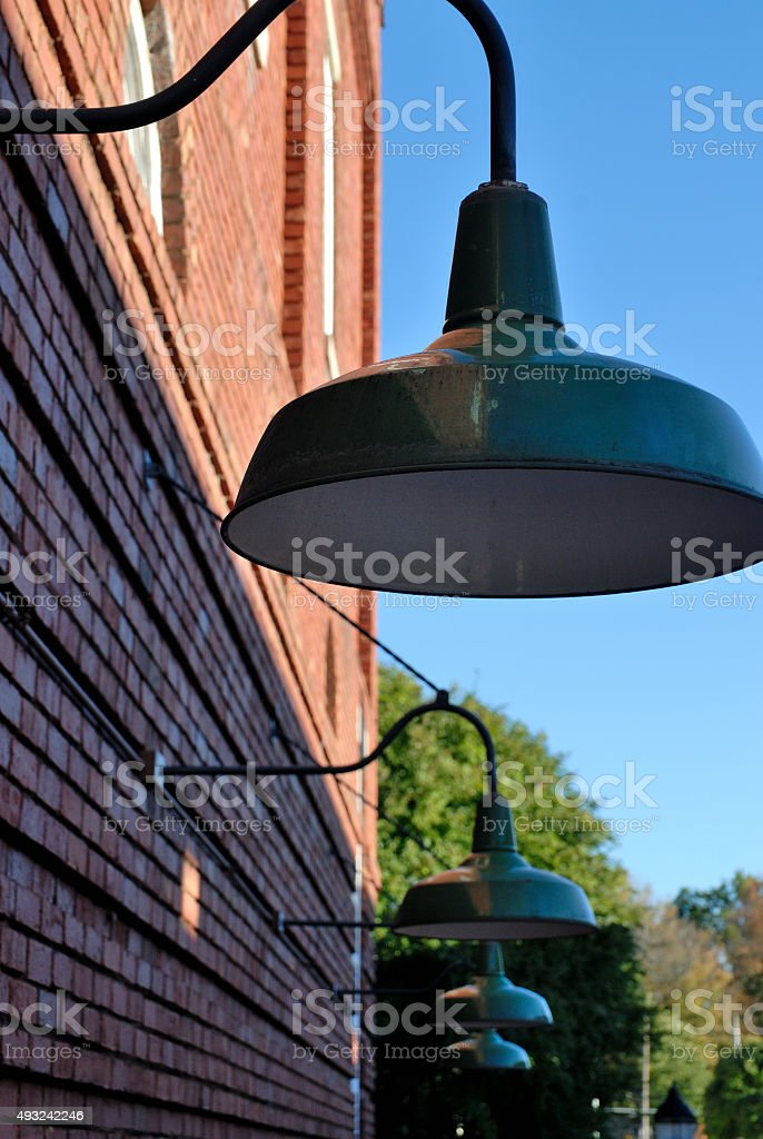 Old style lights handing from building stock photo