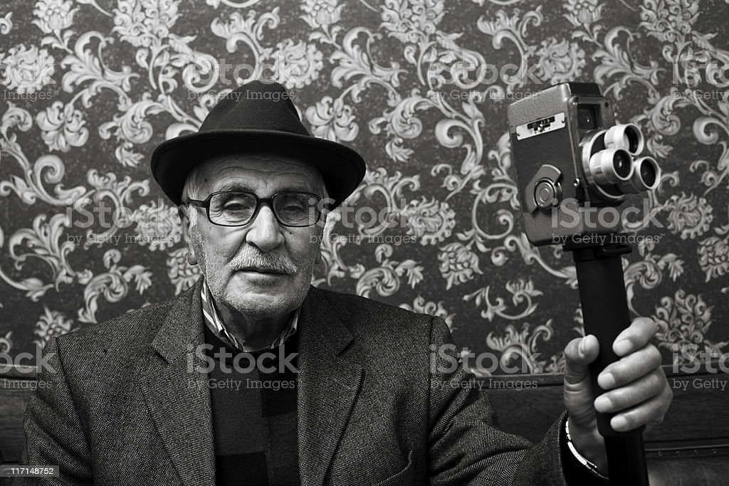 Old style senior videographer posing with his video camera stock photo