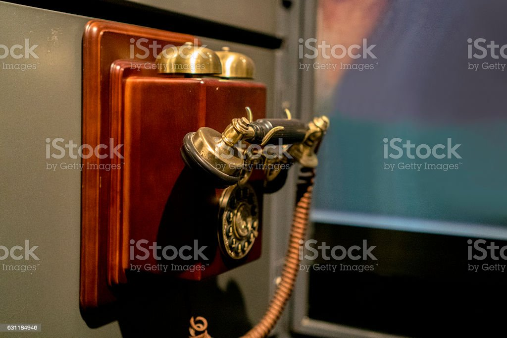 old styled telephone on the wall stock photo