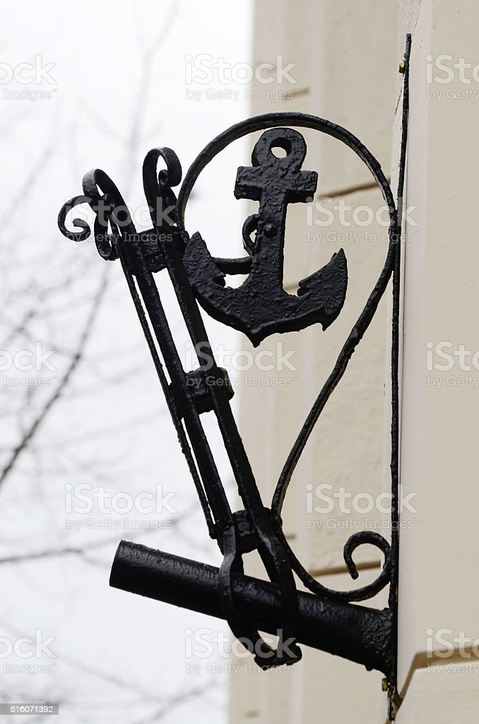 Old stylized flagstaff with anchor on building wall stock photo