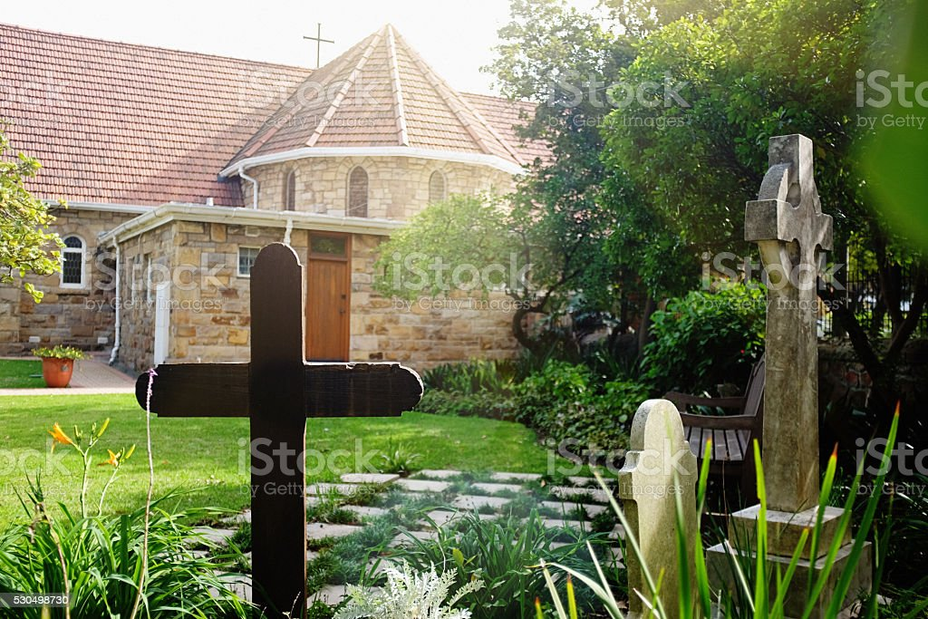Old suburban church with gravestones in the garden stock photo