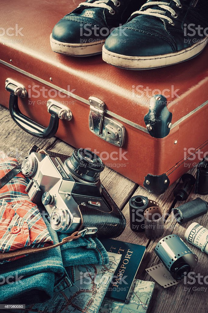 Old suitcase, sneakers, clothing, map, filmstrip and camera stock photo