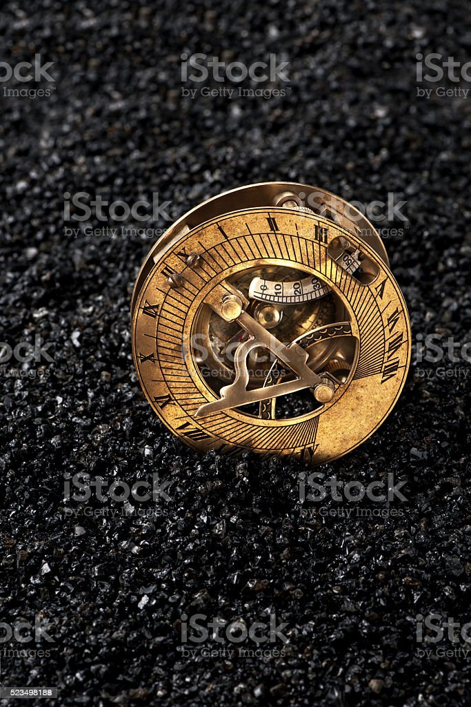 Old sundial with compass on black background stock photo