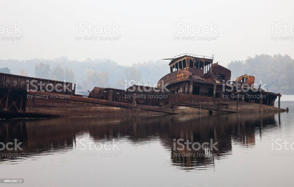 Old sunken ship in water in a foggy day stock photo