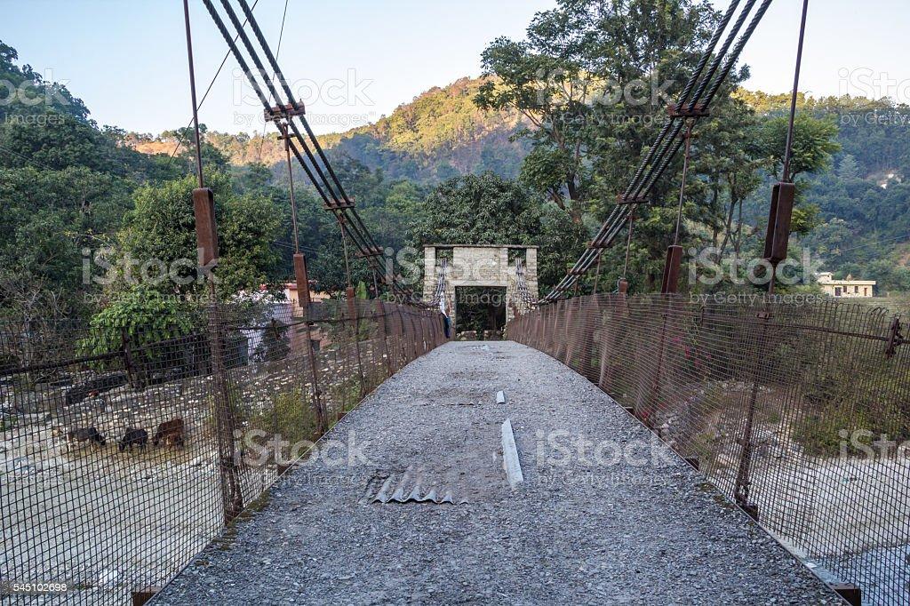 Old suspension bridge over a stream stock photo