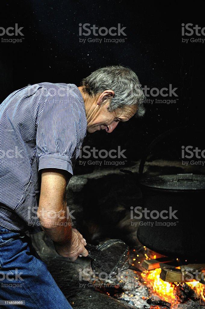 Old Swiss Dairy Farmer FAnning Fire Under Kettle royalty-free stock photo