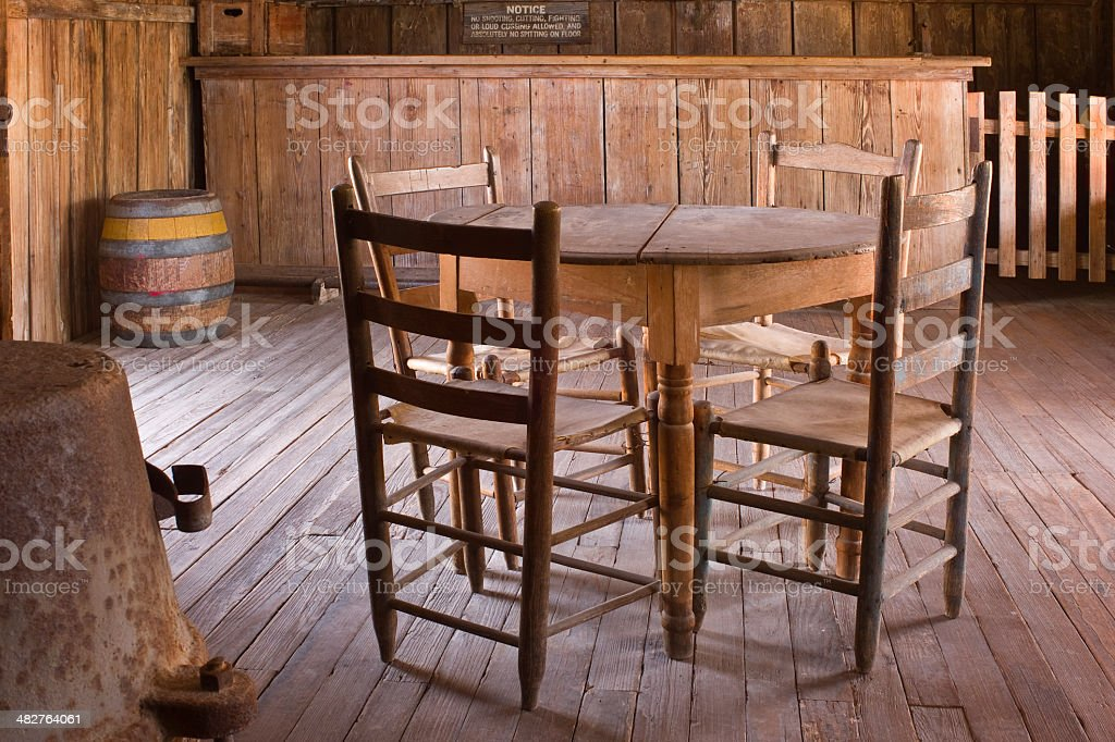 Old Table, Chairs, and Bar at Judge Roy Beans Saloon. stock photo